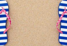 在海滩沙子的五颜六色的塑胶人字平底拖鞋对 免版税库存图片