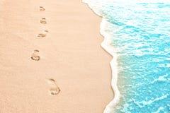 在海滩沙子的人的脚印在手段 免版税库存照片