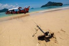 在海滩沙子的小船锚停放的旅游业小船的在海岛 图库摄影