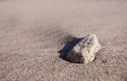 在海滩沙子的岩石 免版税库存图片