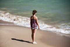 在海滩的一个俏丽的女孩身分和看入海,软的fockus 免版税库存照片
