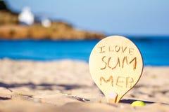 在海滩的一副球拍与书面消息`我爱夏天`,克利特 库存图片