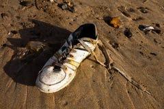 在海滩的一双老体育运动鞋子 图库摄影