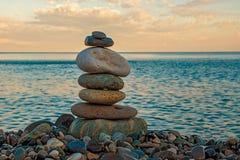 在海滩的一座石金字塔在一个夏天晚上 免版税库存照片