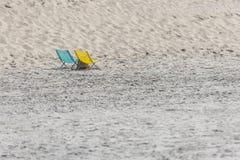 在海滩的一把蓝色和黄色折叠椅 库存照片