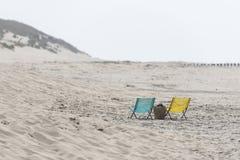 在海滩的一把蓝色和黄色折叠椅 免版税库存照片