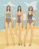 在海滩的三个时装模特儿在镶边sweemsuits 库存照片