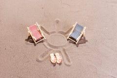 在海滩的两个五颜六色的太阳懒人 免版税库存图片