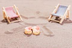 在海滩的两个五颜六色的太阳懒人 免版税库存照片