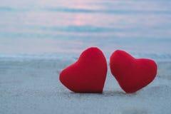 在海滩的两红色心脏 免版税图库摄影