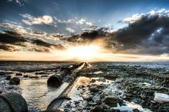 在海滩的严重的日落与对展望期的管道 免版税图库摄影