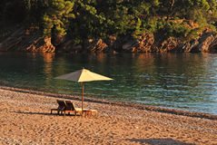 在海滩的二把轻便折叠躺椅和伞。 免版税库存图片