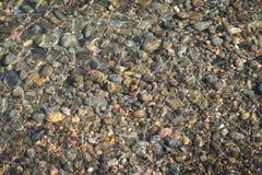 在海滩的五颜六色的小卵石在水中 免版税库存图片