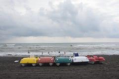 在海滩的五颜六色的pedalo脚蹬小船,阴云密布,云彩,挥动 免版税库存照片