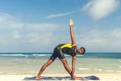在海滩的亚洲瑜伽人实践瑜伽有清楚的蓝天背景 热带海滩的信奉瑜伽者巴厘岛 图库摄影