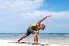 在海滩的亚洲瑜伽人实践瑜伽有清楚的蓝天背景 热带海滩的信奉瑜伽者巴厘岛 免版税库存照片