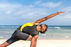 在海滩的亚洲瑜伽人实践瑜伽有清楚的蓝天背景 热带海滩的信奉瑜伽者巴厘岛 免版税库存图片