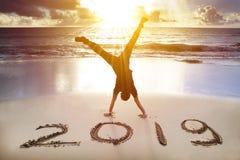 在海滩的人手倒立 新年快乐2019年概念 库存图片