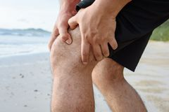 在海滩的人赛跑充满膝盖痛苦 库存照片