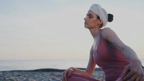 在海滩的传统印度瑜伽由海洋 东方东部出现的美女是思考的一会儿 股票录像