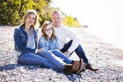 在海滩的偶然年轻家庭 库存照片