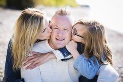 在海滩的偶然年轻家庭 免版税库存照片