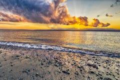 在海滩的充满活力的日落 免版税库存照片
