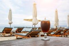 在海滩的可乐玻璃与伞 ?? 库存照片