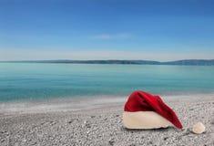 在海滩的圣诞节帽子 免版税库存图片