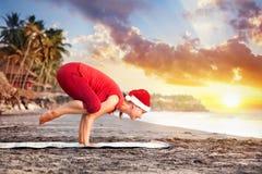 在海滩的圣诞节瑜伽 库存照片
