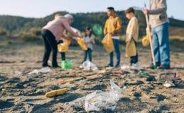 在海滩的塑料与小组志愿者 免版税库存图片