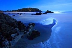 在海滩的夜:月亮和岩石照亮的浪潮水池 免版税图库摄影