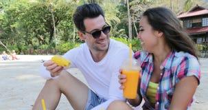 在海滩的夫妇吃热带水果谈话坐在棕榈树下的饮料汁液,愉快的人和妇女游人通信 股票录像