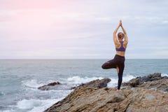 在海滩的女子实践的瑜伽日落 免版税图库摄影