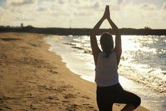在海滩的女性瑜伽在日出 库存图片