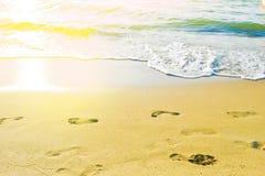 在海滩的女性脚印反对向海 免版税库存照片