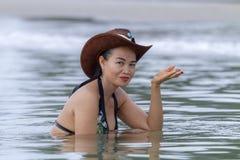 在海滩的妇女和帽子俏丽的比基尼泳装 图库摄影
