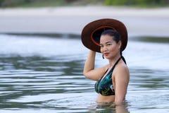 在海滩的妇女和帽子sexsy标志比基尼泳装 免版税库存图片