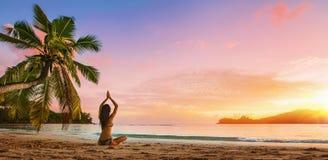 在海滩的妇女实践的莲花姿势 免版税图库摄影