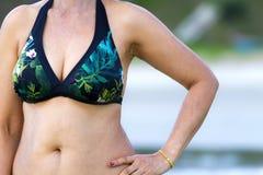 在海滩的妇女形状俏丽的样式比基尼泳装 免版税库存照片