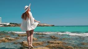 在海滩的妇女旅游白色礼服身分用透明的水 股票视频