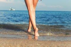 在海滩的妇女的美好的性感的腿 免版税库存照片