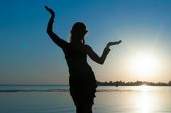 在海滩的妇女跳舞部族舞蹈在黎明 免版税库存照片