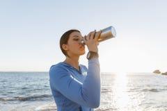在海滩的妇女饮用水 免版税图库摄影