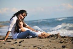 在海滩的妈妈和女儿纵向 免版税库存照片