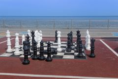 在海滩的室外棋由在人的成长的海高度 免版税库存照片