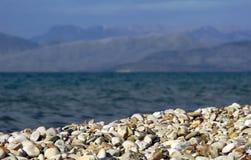 在海滩的小卵石在Corfu海岛 免版税库存图片