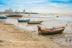 在海滩的小渔船与都市风景和明亮的天空背景 库存图片