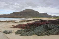 在海滩的岩石在山和云彩 免版税库存照片