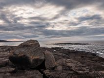 在海滩的岩石在日落在一多云天在Marquette,密执安 免版税库存图片